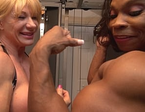 Female bodybuilders Wild Kat and Nadia are in the gym when Nadia brings out her strap-on ebony dildo. Nadia masturbates Wild Kat's big clit with the toy, then penetrates Kat from behind while you enjoy the vascular, mature muscles of their pecs, legs, glutes, biceps and abs and watch the hot girl/girl sex in close-up.