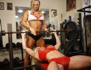 Bodybuilders Ashlee Chambers and Darkside Milinda start a super workout in the gym wearing panties, but soon they're naked and posing, showing off their sexy pecs, big biceps and vascular, shredded abs and their tattoos, and bench pressing with their legs wide open, so they can see each other's pretty kitties and so can you. Time for some super girl/girl for these women of steel?