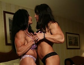Bodybuilders Lynn McCrossin and Roxie Rain get passionate in the bedroom. They're both wearing purple bras, but those go fast as they suck each other's nipples, then pull their panties aside for some mutual girl/girl masturbation of their big clits and tight asses, giving you a nice look at the legs, glutes and vascular biceps you love.