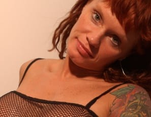 In the bedroom, tattooed Petra spreads her muscular legs, giving you a good close-up look at her wet pussy and big clit. Then she straps on a big black dildo and a girlfriend joins her, sucking on the toy and getting into some girl/girl getting it on. You can get into that, can't you?