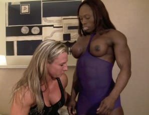 Bodybuilders Darkside Milinda and Mistress Treasure meet in the bedroom for some girl/girl muscle worship as they stroke each other's pecs, biceps, glutes and tattooed abs. Treasure pulls aside Milinda's panties,  masturbates her big clit, and promises her – and you – much more.